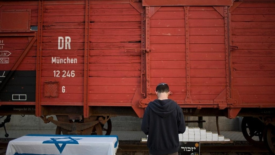 A man prays next to a wagon from WWII on display on the eve of Holocaust Remembrance Day in Netanya, Israel, Wednesday, April 15, 2015. The wagon München 12 246 was built in Germany in the early 20th century to transport cattle. During World War II thousands of people were transported in it to the death camps. The wagon was bought in Germany and transported to Israel in 2014. (AP Photo/Ariel Schalit)