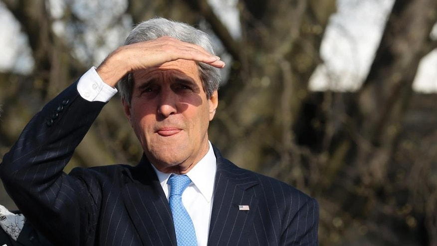 United States Secretary of State John Kerry shields his eyes against the sun as he uses a boat on his way to a working session during a meeting of the G7 Foreign Ministers in Luebeck, northern Germany, Wednesday, April 15, 2015. The meeting is being held ahead of the G7 leaders summit in Germany from June 7 to 8, 2015. (AP Photo/Markus Schreiber)