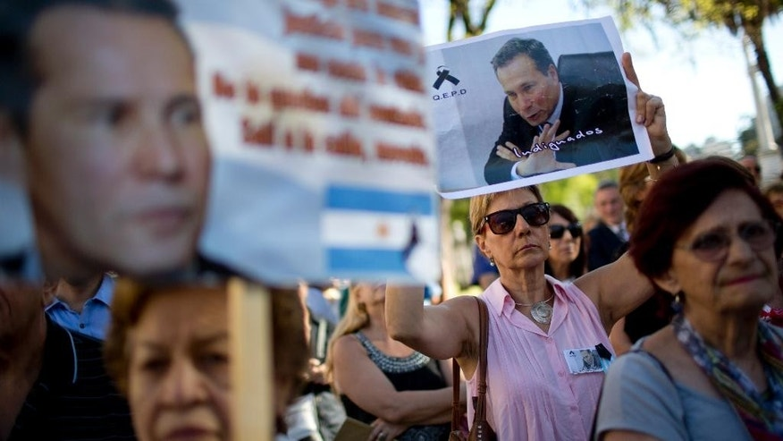 FILE - In this March 18, 2015 file photo, demonstrators hold images of the late prosecutor Alberto Nisman during an act to demand justice after more than a month after his death, outside the court house in Buenos Aires, Argentina. The discovery of a gun in a storage area is raising new questions about the death of the prosecutor. Nisman's ex-wife Sandra Arroyo Salgado says the discovery of the prosecutor's own weapon bolsters her contention that Nisman did not commit suicide, since he wouldn't have needed to borrow the weapon that killed him. Investigators say are they investigating both homicide and suicide. (AP Photo/Natacha Pisarenko, File)