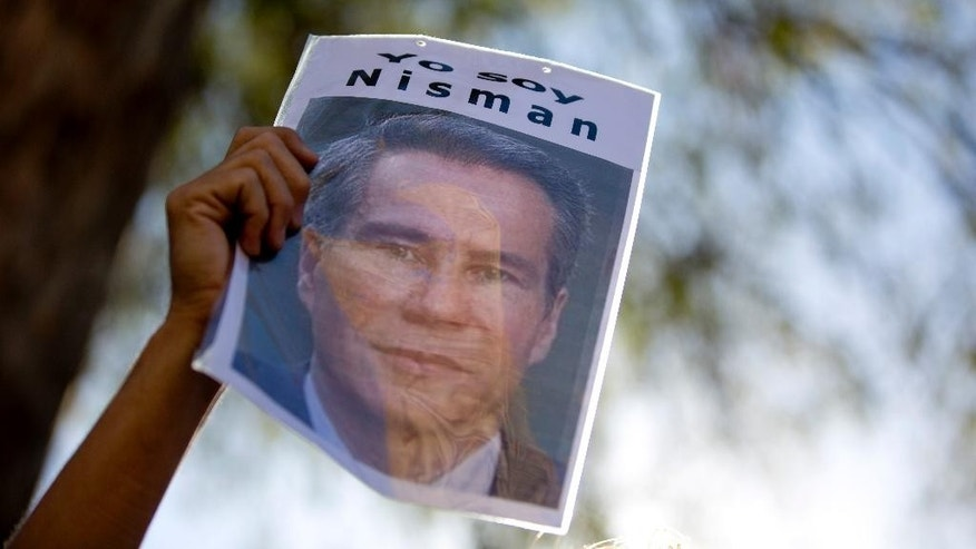 "FILE - In this March 18, 2015 file photo, a demonstrator holds a sign that reads in Spanish ""I am Nisman"" during an act to demand justice following the death of special prosecutor Alberto Nisman, outside court in Buenos Aires, Argentina. Days before the three month mark since his mysterious death, Argentina's Supreme Court President Ricardo Lorenzetti urged investigators to solve the circumstances of Nisman's death on Monday, April 13, 2015. Nisman was found dead in his bathroom on Jan. 18, on the eve of congressional hearings where he was due to present his accusations against President Cristina Fernandez of shielding Iranian officials from prosecution over the 1994 bombing of a Buenos Aires Jewish centre. (AP Photo/Natacha Pisarenko, File)"