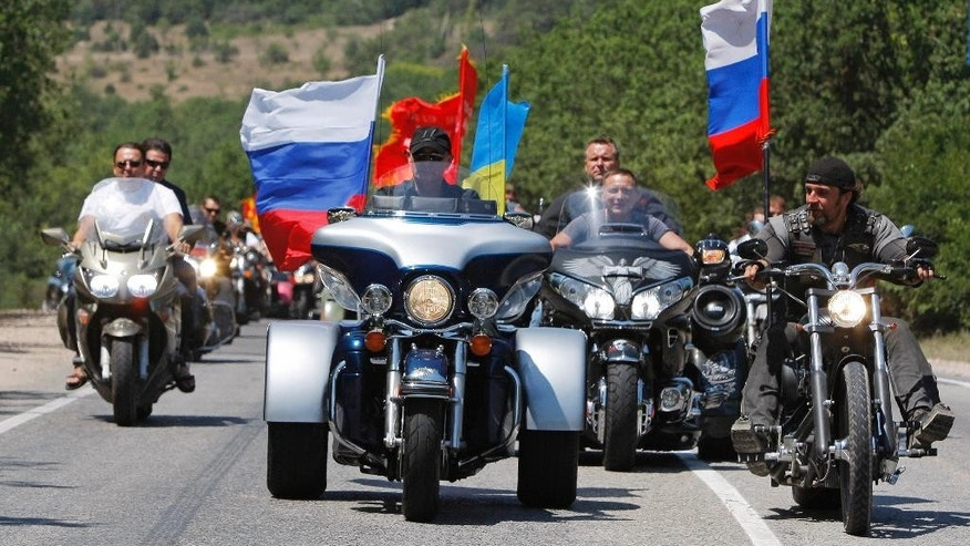 FILE - In this file photo taken on Saturday, July  24, 2010, then Russian Prime Minister Vladimir Putin rides three wheeler at centre,  accompanied by the Night Wolves biker group leader Alexander Zaldostanov, right,  at Gasfort near Sevastopol, Crimea.  Poland's Prime Minister Ewa Kopacz spoke out Wednesday April 15, 2015, against plans by Russian nationalistic Night Wolves biker group to ride through Poland on a journey to Berlin to mark the 70th anniversary of the Soviet victory over Nazi Germany. The Night Wolves, a nationalistic group loyal to Russian President Vladimir Putin, plan to retrace the westward path that Red Army soldiers took across eastern Europe as they fought Nazi troops.  (AP Photo/Alexander Zemlianichenko, Pool, FILE)