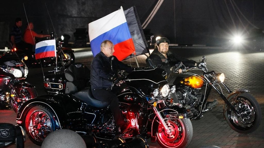 FILE - In this file photo taken on Monday, Aug.  29, 2011, then Russian Prime Minister Vladimir Putin rides three wheeler at centre,  accompanied by the Night Wolves biker group leader Alexander Zaldostanov, right, at Novorossiysk, Russia.  Poland's Prime Minister Ewa Kopacz spoke out Wednesday April 15, 2015, against plans by Russian nationalistic Night Wolves biker group to ride through Poland on a journey to Berlin to mark the 70th anniversary of the Soviet victory over Nazi Germany. The Night Wolves, a nationalistic group loyal to Russian President Vladimir Putin, plan to retrace the westward path that Red Army soldiers took across eastern Europe as they fought Nazi troops.  (AP Photo/Ivan Sekretarev, Pool, FILE)