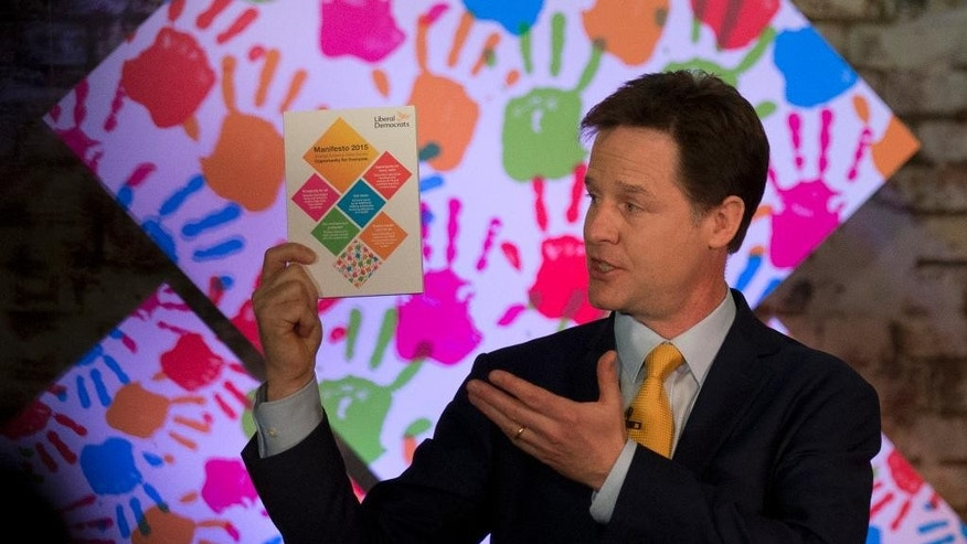 Nick Clegg the leader of Britain's Liberal Democrats party holds up a copy of his party's manifesto during its launch in London, Wednesday, April 15, 2015.  Britain goes to the polls in a General Election on May 7.  (AP Photo/Matt Dunham)