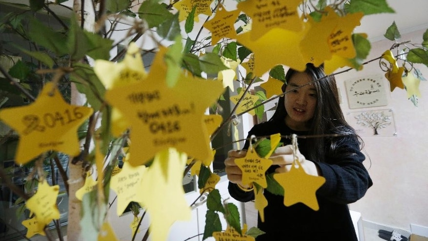 "In this April 10, 2015 photo,  Choi Yun-ah, sister of Danwon High School student Choi Yun-min, who died in the sinking of ferry Sewol, hangs a note of tribute  for missing passengers and victims on a tree in Ansan, South Korea. Siblings, she says, often have no one else to turn to because they are afraid of putting more of a burden on their grieving parents. ""Siblings are victims too, but no one in the world knows about it.""  The Sewol ferry sank on April 16, 2014, killing 304 people including 250 Danwon High School students on a school trip. (AP Photo/Ahn Young-joon)"