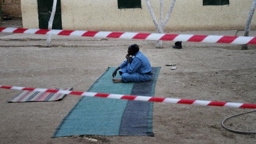 A member of Sudanese security forces rests after praying outside a polling station,,on the third day of Sudan's presidential and legislative elections in Khartoum, Sudan, Wednesday, April 15, 2015. Sudan's election commission has extended voting to one more day, after three-day vote witnessed low turnout. (AP Photo/Abd Raouf)