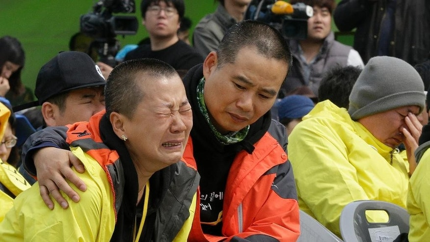 A relative of the victims of the Sewol disaster weeps during a ceremony on the eve of the first anniversary of the ferry sinking at a port in Jindo, South Korea, Wednesday, April 15, 2015. A year ago, as South Korea writhed in grief and fury after more than 300 people, most of them school kids, drowned in the disaster, it seemed things would never be the same. Yet not much has really changed as the first anniversary of the Sewol disaster is marked Thursday. (AP Photo/Ahn Young-joon)