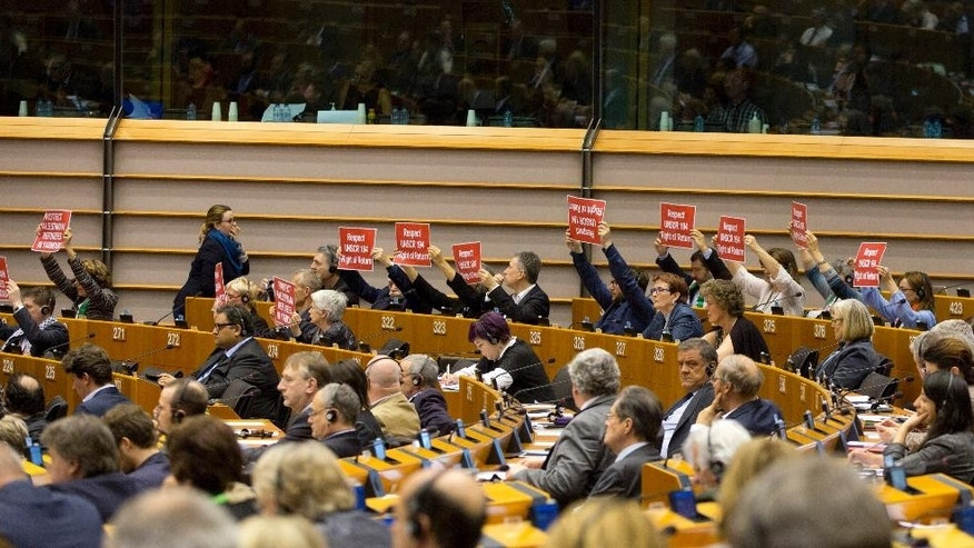 "Members of European Parliament hold signs which read ""Respect UNSCR 194 Right of Return"" and ""Respect Palestinian refugees in Yarmouk"" during a plenary session at European Parliament in Brussels on Wednesday, April 15, 2015. MEP's on Wednesday will discuss the Multi-annual Financial Framework for 2014-2020, the anniversary of the Bangladesh factory fire and an estimated 1.5 million Armenians who were killed by Ottoman Turks around the time of World War I. (AP Photo/Virginia Mayo)"