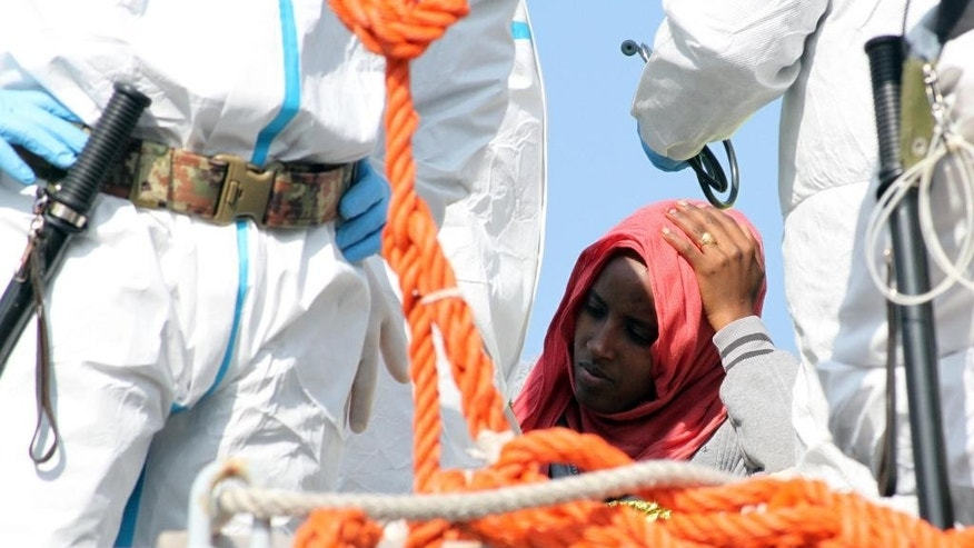 In this picture taken on Tuesday, April 14, 2015 a woman waits to disembark from an Italian Navy vessel in the harbor of Reggio Calabria, southern Italy. The precise number of migrants who have perished in the Mediterranean sea as they flee poverty, war and other conflicts in Africa, the Middle East and Asia is unknown. Only the bodies that wash ashore or are found drowned in the sea or dead aboard, of thirst or exposure, by rescuers are counted. (AP Photo/Adriana Sapone)