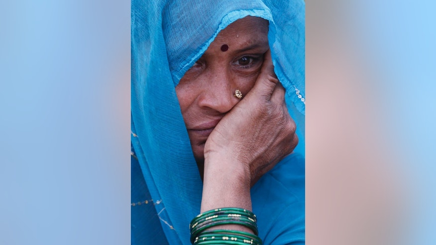 In this Tuesday, April 14, 2015 photo  Indian farmer woman, Gudia Yadav, 50 reacts after seeing her damaged wheat crop damaged in unseasonal rain at Malaca village, outskirts of Allalhabad, Uttar Pradesh state, India. April is usually a time of celebration for millions of farmers across northern India. The winter wheat crop is ready to be harvested, and there's money to clear past debts and plan future planting.This year, however, unseasonal rain and hailstorms in March destroyed millions of acres of farmland in the region, leaving dozens of distraught farmers to kill themselves. (AP Photo/ Rajesh Kumar Singh)