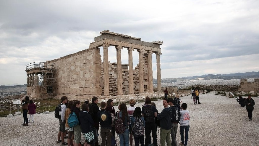 Tourists listen to a guide as they stand in front of the Erechtheion temple during a visit at the Acropolis hill in Athens, on Wednesday, April 15, 2015. Vacations in Europe have a new attraction: the euro's steep drop in value is making the continent cheaper for tourists from across the world, especially the United States and China. For American tourists, the dollar's strength translates into a discount of around 25 percent compared with this time last year. China's currency has risen some 20 percent against the euro over the past year. (AP Photo/Yorgos Karahalis)