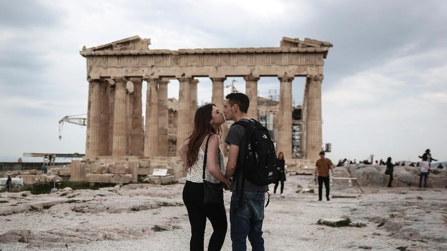 U.S. visitors Zach Branch,19, right, and Madison Franklin, 18, both from California, kiss in front of the Parthenon during their visit at the Acropolis hill in Athens, on Wednesday, April 15, 2015. Vacations in Europe have a new attraction: the euro's steep drop in value is making the continent cheaper for tourists from across the world, especially the United States and China. Branch said that as a U.S. citizen is much cheaper to travel to Europe now, than it was two years ago. (AP Photo/Yorgos Karahalis)
