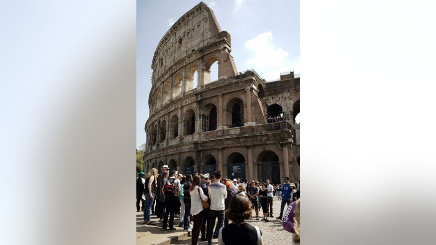 In this photo taken on Friday, April 10, 2015, people line up to enter the Colosseum, in Rome. Vacations in Europe have a new attraction: the euro's steep drop in value is making the continent much cheaper for tourists from across the world, especially the United States and China. For American tourists, the dollar's strength translates into a discount of around 25 percent compared with this time last year. China's currency has risen some 20 percent against the euro over the past year. (AP Photo/Andrew Medichini)