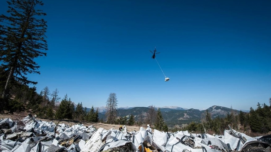 April 13, 2015: A helicopter carries bags loaded with debris of the Germanwings passenger jet, gathered near the crash site in Seyne-les-Alpes, France.