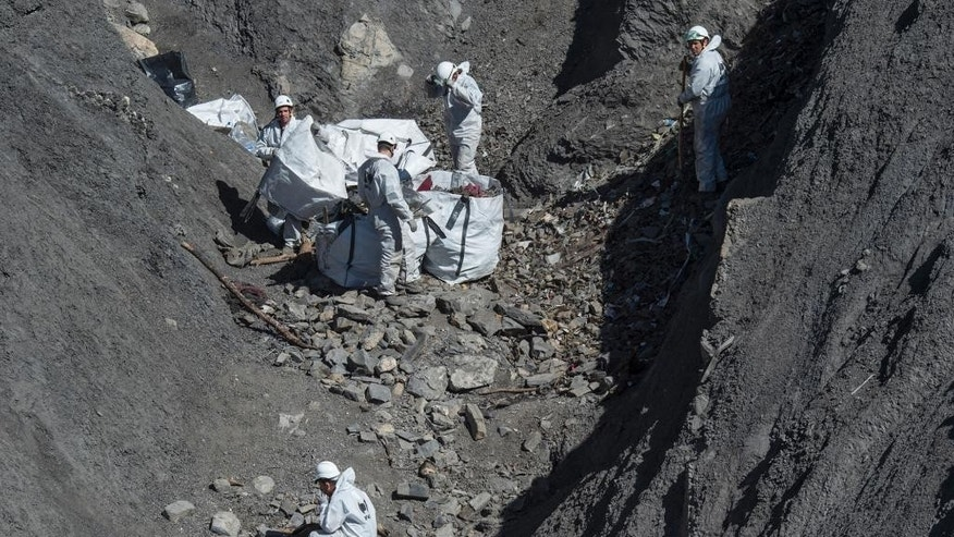 April 13, 2015: French emergency rescue services collect debris of the Germanwings passenger jet at the crash site near Seyne-les-Alpes, France.