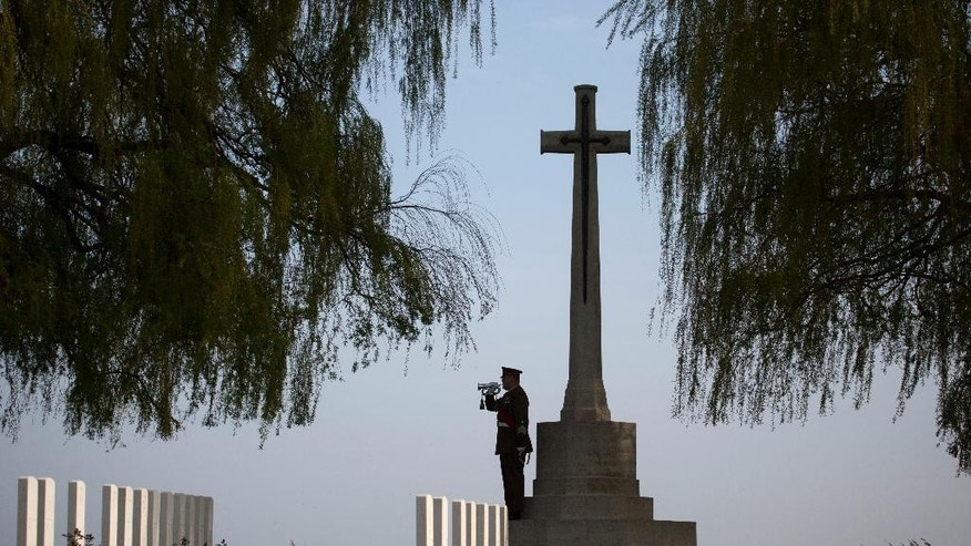 British Drum Major Paul Ingleton plays the Last Post during a reburial ceremony for six British World War I soldiers at Prowse Point cemetery in Ploegsteert, Belgium on Thursday, April 16, 2015. Six British unknown soldiers were buried Thursday more than 100 years after they fell in 1914. Two were identified as from the Lancashire Fusiliers and two from the King's Own Royal Lancaster Regiment. (AP Photo/Virginia Mayo)