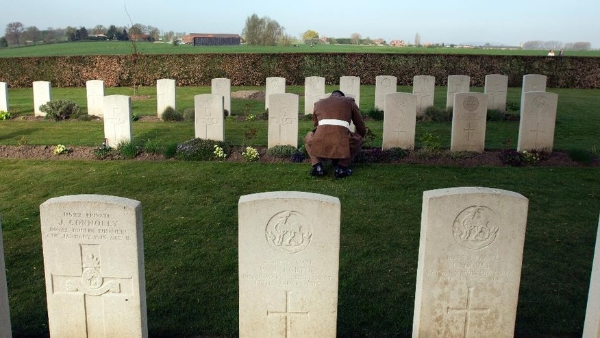 A British soldiers pays respects at a grave during a reburial ceremony for six World War I soldiers at Prowse Point cemetery in Ploegsteert, Belgium on Thursday, April 16, 2015. Six British unknown soldiers were buried Thursday more than 100 years after they fell in 1914. Two were identified as from the Lancashire Fusiliers and two from the King's Own Royal Lancaster Regiment. (AP Photo/Virginia Mayo)