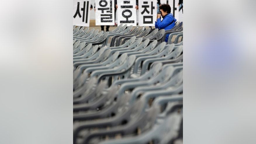 "A woman wipes her tears outside a group memorial altar for the victims of the sunken ferry Sewol, in Ansan, South Korea, Thursday, April 16, 2015. With tears, lowered flags and still-fresh anger, relatives mourned the 300 people, mostly high school kids, killed one year ago when the ferry Sewol sank in cold waters off the southwestern South Korean coast. The letters read ""Disaster, Ferry Sewol."" (AP Photo/Lee Jin-man)"