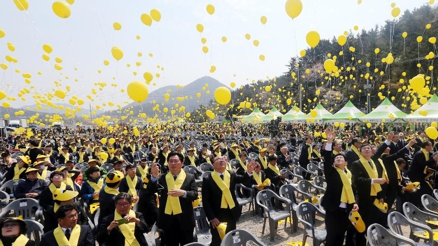 People release balloons during a ceremony to commemorate the first anniversary of the Sewol ferry sinking at a port in Jindo, South Korea, Thursday, April 16, 2015. Tears and grief mixed with raw anger Thursday as black-clad relatives mourned the 300 people, mostly high school kids, killed one year ago when the ferry Sewol sank in cold waters off the southwestern South Korean coast. (Park Chul-hong/Yonhap via AP) KOREA OUT