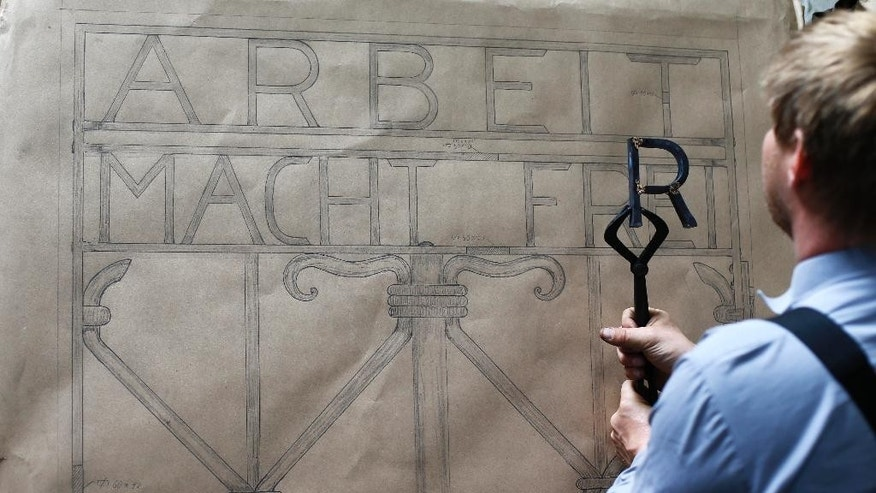 "Blacksmith Michael Poitner works on a replica of the Dachau Nazi concentration camp gate with the writing ""Arbeit macht frei"" (Work Sets you Free) in Biberbach near Dachau, Germany, Thursday, April 16, 2015. The original gate was stolen  in November 2014. (AP Photo/Matthias Schrader)"