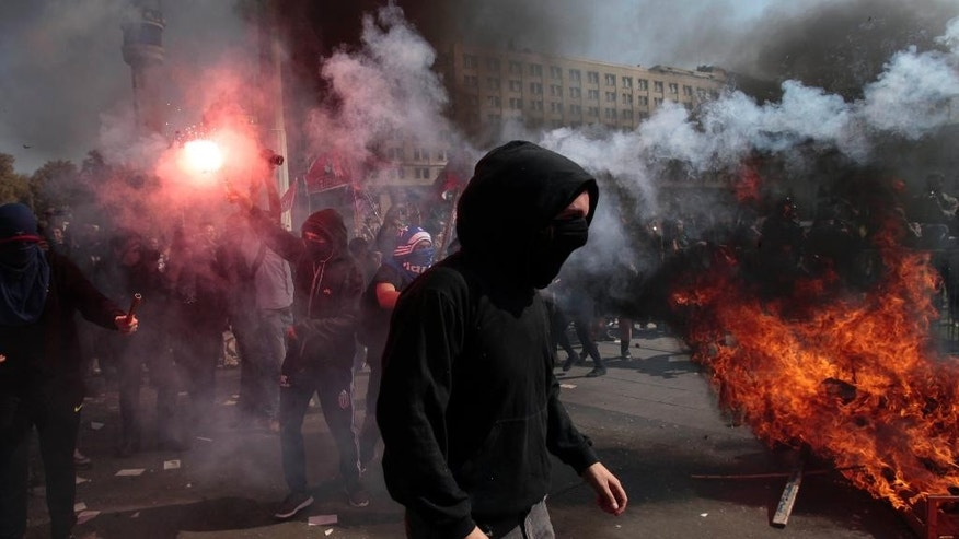 A protester holds a flare near La Moneda Palace during a protest march, in Santiago, Chile, Thursday, April 16, 2015. Thousands of students marched through the streets of Chile's capital to protest recent corruption scandals and to complain about delays in a promised education overhaul. While it was largely peaceful, violence broke out at the end when hooded protesters threw rocks and gasoline bombs at police. At least one officer was injured. (AP Photo/Luis Hidalgo)