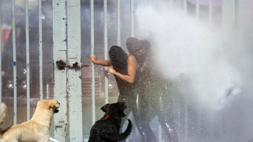 Protesters are drenched with water from a water cannon operated by police during clashes in the courtyard of the University of Santiago, during a demonstration in Santiago, Chile, Thursday, April 16, 2015. Thousands of students marched through the streets of Chile's capital to protest recent corruption scandals and to complain about delays in a promised education overhaul. While it was largely peaceful, violence broke out at the end when hooded protesters threw rocks and gasoline bombs at police. At least one officer was injured. (AP Photo/Luis Hidalgo)