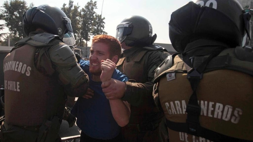 A protester is detained by police during a demonstration in Santiago, Chile, Thursday, April 16, 2015. Thousands of students marched through the streets of Chile's capital to protest recent corruption scandals and to complain about delays in a promised education overhaul. While it was largely peaceful, violence broke out at the end when hooded protesters threw rocks and gasoline bombs at police. At least one officer was injured. (AP Photo/Luis Hidalgo)