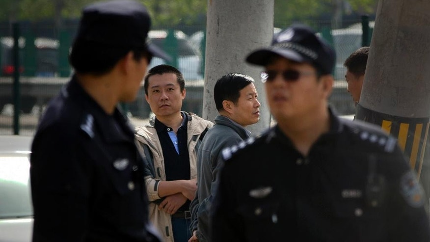 Men wait as Chinese policemen stand guard near the Beijing No. 3 Intermediate Court in Beijing, Friday, April 17, 2015. Veteran Chinese journalist Gao Yu was sentenced to seven years in prison Friday for leaking a document detailing the Communist Party leadership's resolve to aggressively target civil society and press freedom as a threat to its monopoly on power. (AP Photo/Mark Schiefelbein)