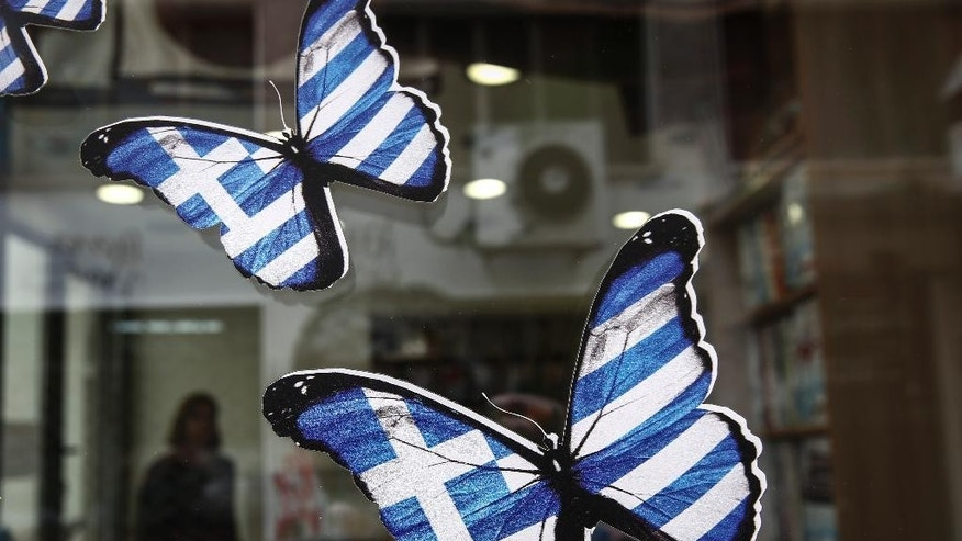 A woman stands inside a shop behind stickers depicting butterflies with the colors of the Greek flag in Athens, on Wednesday, April 15, 2015. Greece's new left wing-led government has been locked in strained negotiations with creditors since winning elections in January on pledges to abolish the deeply resented budget austerity measures required by the rescue program. (AP Photo/Yorgos Karahalis)