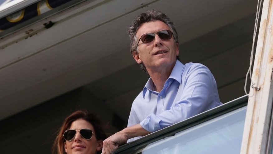 FILE - In this Nov. 3, 2012 file photo, Buenos Aires' Mayor Mauricio Macri, right, and his wife Juliana Awada, watch a national league soccer match between Boca Juniors and San Lorenzo, in Buenos Aires, Argentina. Macri, the man who could be Argentina's next president wants to put an end to tight government currency controls, make peace with the nation's creditors and improve severely frayed ties to the United States. In short, the right-leaning Buenos Aires mayor is promising to undo much of what President Cristina Fernandez and her late husband Nestor Kirchner created over the past 13 years. (AP Photo/Victor R. Caivano, File)