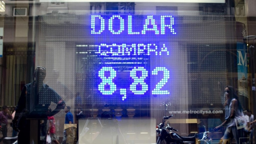 """In this April 10, 2015 photo, people are reflected in the store front window of an exchange house in Buenos Aires, Argentina. Presidential candidate Mauricio Macri says if he is elected in October, he would move quickly to restrictions on Argentines' ability to trade pesos for U.S. dollars. But critics warn against doing too much, too fast. Lifting currency controls overnight could spark a bank run and unleash a financial """"bloodbath,"""" according to former Central Bank President Aldo Pignanelli. (AP Photo/Natacha Pisarenko)"""