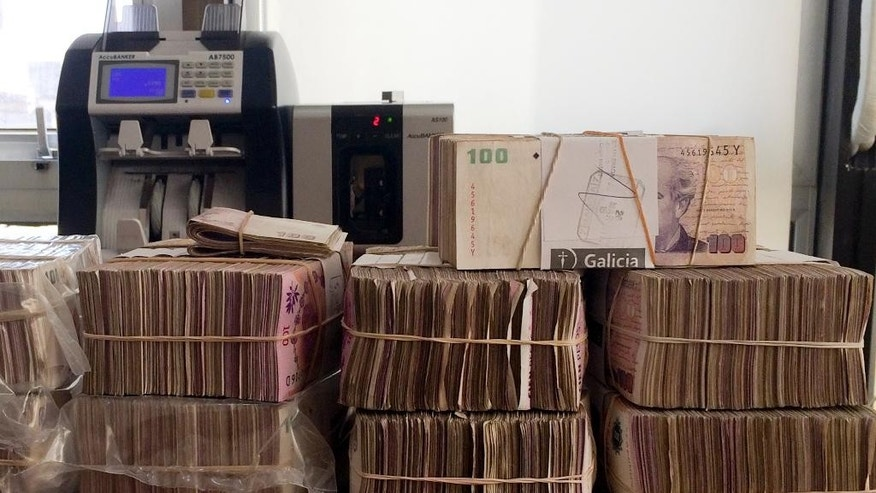 In this April 10, 2015 photo, thousands of Argentine pesos are seen in an illegal exchange house in Buenos Aires, Argentina. Many Argentines trade pesos for dollars on the black market because of high inflation and because the government restricts the sale of dollars from the banks. Leading presidential candidate Mauricio Macri has said that if elected he would lift restrictions on buying dollars. (AP Photo/Peter Prengaman)
