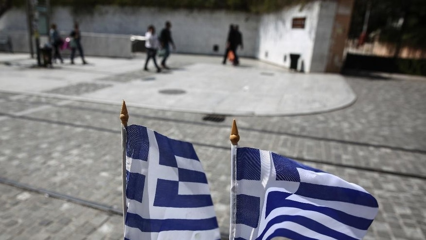Greek flags flutter as people walk down a central pedestrian street of Athens, on Tuesday, April 14, 2015. Greece's new left wing-led government has been locked in strained negotiations with creditors since winning elections in January on pledges to abolish the deeply resented budget austerity measures required by the rescue program. (AP Photo/Yorgos Karahalis)