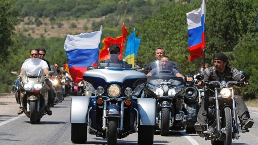 FILE - In this file photo taken on Saturday, July  24, 2010, then Russian Prime Minister Vladimir Putin rides three wheeler at center, accompanied by the Night Wolves biker group leader Alexander Zaldostanov, right,  at Gasfort near Sevastopol, Crimea. (AP Photo/Alexander Zemlianichenko, Pool, FILE)