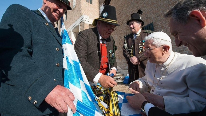 April 15, 2015: Pope Emeritus Benedict XVI, right, receives a Bavarian flag by members of a group from his hometown Bavaria region, on the occasion of his 88th birthday, in the pontiff's Castel Gandolfo residence, in the hills overlooking Rome.