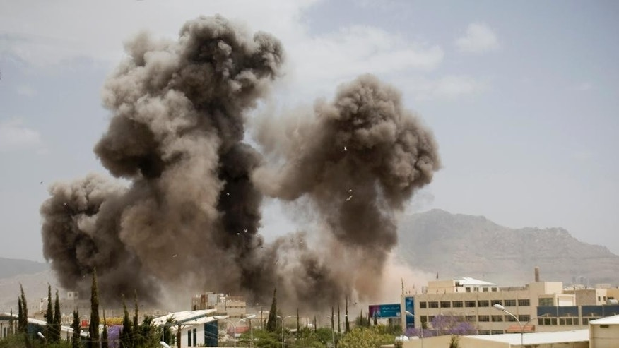 FILE - In this Wednesday, April 8, 2015 file photo, smoke billows from a Saudi-led airstrike in Sanaa, Yemen. Saudi Arabia's government insists it is not at war with Iran despite its three-week air campaign against Tehran-backed rebels in Yemen, but the kingdom's powerful clerics, and its regional rival's theocratic government, are increasingly presenting the conflict as part of a region-wide battle for the soul of Islam. (AP Photo/Hani Mohammed, File)