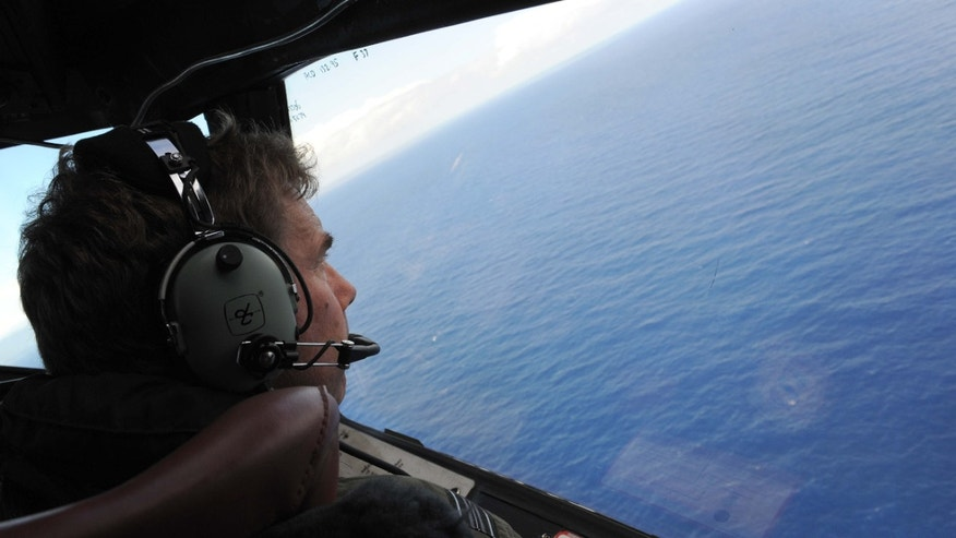 April 13, 2014: In this photo taken from the Royal New Zealand air force (RNZAF) P-3K2-Orion aircraft, co-pilot Squadron Leader Brett McKenzie looks out of a window while searching for debris from missing Malaysia Airlines Flight 370, in the Indian Ocean off the coast of western Australia.