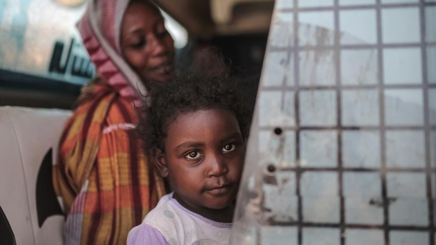 In this picture taken Tuesday, April 14, 2015, a Sudanese girl looks out of the window while waiting with her mother in a public bus in Izba, an impoverished neighborhood on the outskirts of Khartoum, Sudan. Izba is one sign of how the constant internal wars, under Sudan's President Omar al-Bashir, have shaped, Khartoum. Before al-Bashir came to power, Izba was home to a community of Arab tribesmen who had settled here to be close to the capital. But through the 1990s and 2000s, it swelled with Sudanese fleeing war zones around the country. Now 70,000 people live crammed into Izba, an area of about a square mile. (AP Photo/Mosa'ab Elshamy)