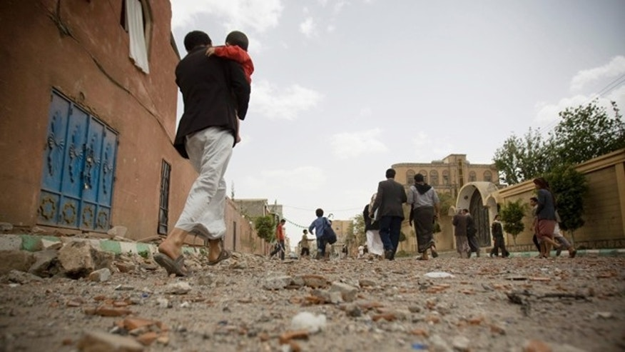 FILE - In this Wednesday, April 8, 2015 file photo, people flee after a Saudi-led airstrike in Sanaa, Yemen. (AP Photo/Hani Mohammed, File)