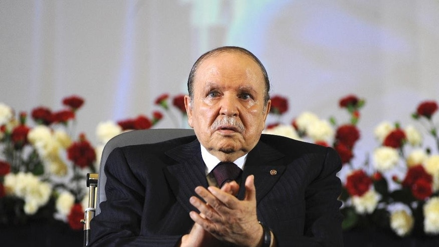 FILE - In this April 28, 2014 file photo, Algerian President Abdelaziz Bouteflika, sitting in a wheelchair, applauds after taking the oath as President in Algiers.  One year after he was re-elected to a fourth term, the absence of Algeria's stroke-hit president from daily life is being felt more keenly than ever as this oil-rich North African nation is facing unprecedented economic and political challenges. (AP Photo/Sidali Djarboub, File)
