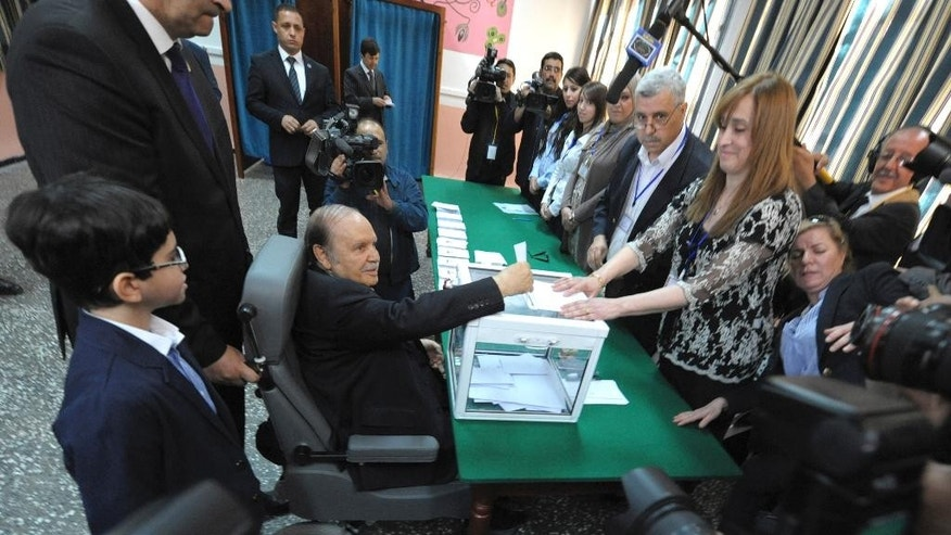 FILE - In this April 17, 2014 file photo, Algeria's President Abdelaziz Bouteflika, sitting on a wheelchair,  votes in the presidential elections in Algiers. One year after he was re-elected to a fourth term, the absence of Algeria's stroke-hit president from daily life is being felt more keenly than ever as this oil-rich North African nation is facing unprecedented economic and political challenges. (AP Photo/Sidali Djarboub, File)