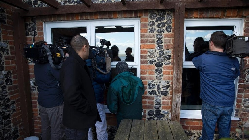 Television broadcasters try to film Nigel Farage, the leader of the UK Independence Party (UKIP) through the windows of the Coastguard pub after they were not allowed to follow him in there after he unveiled a poster for his party's immigration campaign launch for the British general election, in St Margaret's Bay, near Dover, on the south east coast of England, Tuesday, March 31, 2015.  (AP Photo/Matt Dunham)