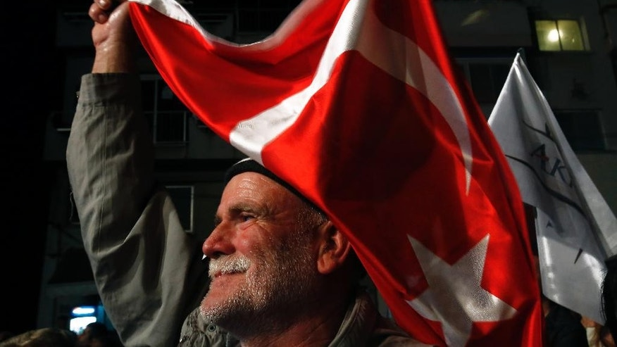 FILE - This is a Tuesday, April 14, 2015  file photo of a supporter of the leadership candidate Mustafa Akinci as he waves a Turkish flag during a rally in the old city of the divided capital of Nicosia at the Turkish Cypriot north part of the island of Cyprus.  Uncertainty reigns as Turkish Cypriots vote for a new leader this weekend: There's no clear favorite and no way of knowing whether the winner can bring talks on reunifying Cyprus to a successful conclusion. (AP Photo/Petros Karadjias, File)