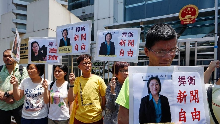 "Anti-Beijing protesters hold pictures of jailed veteran Chinese journalist Gao Yu during a rally outside Chinese central government's liaison office in Hong Kong Friday, April 17, 2015 as they demand press freedom and the release of Gao. A court in Beijing on Friday sentenced Gao to seven years in prison for leaking a top Communist Party document that outlined the leadership's resolve to aggressively curb civil society and press freedom. The placards read ""Defend press freedom. "" (AP Photo/Kin Cheung)"