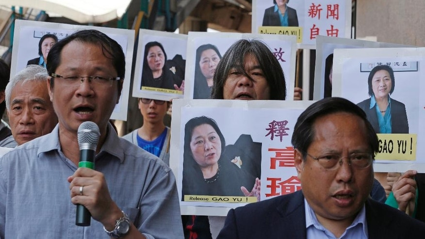 "Anti-Beijing protesters hold pictures of jailed veteran Chinese journalist Gao Yu during a rally near Chinese central government's liaison office in Hong Kong Friday, April 17, 2015 as they demand press freedom and the release of Gao. A court in Beijing on Friday sentenced Gao to seven years in prison for leaking a top Communist Party document that outlined the leadership's resolve to aggressively curb civil society and press freedom. The placards read ""Defend press freedom. "" (AP Photo/Kin Cheung)"