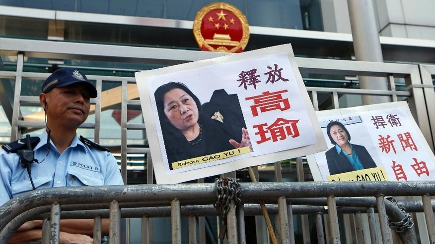 "Pictures of jailed veteran Chinese journalist Gao Yu are displayed by protesters outside Chinese central government's liaison office in Hong Kong Friday, April 17, 2015. A court in Beijing on Friday sentenced Gao to seven years in prison for leaking a top Communist Party document that outlined the leadership's resolve to aggressively curb civil society and press freedom. The placards read ""Release Gao Yu"" and ""Defend press freedom."" (AP Photo/Kin Cheung)"