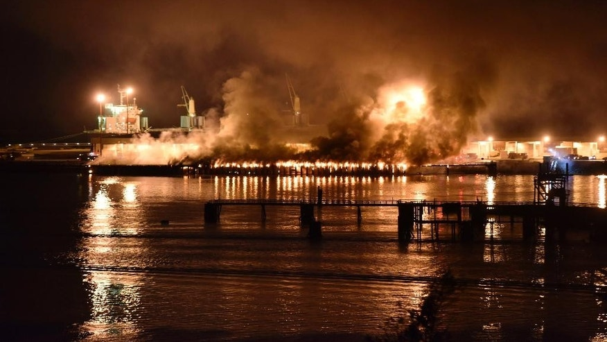 A significant amount of dark and smelly smoke from a fire at a deep-water port terminal billowed over the town of Squamish, British Columbia, Thursday night April 16, 2015, forcing municipal officials to ask residents to stay indoors. (The Canadian Press, Silvester Law via AP)