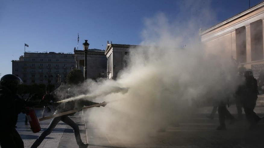 A protester sprays a fire extinguisher at police during a rally in front of the Athens University, which is under occupation by protesters, in Athens, Thursday, April 16, 2015.  Leftist and anarchist groups seeking the abolition of new maximum security prisons, clashed in central Athens Thursday with riot police, who responded with tear gas and stun grenades. (AP Photo/Yorgos Karahalis)