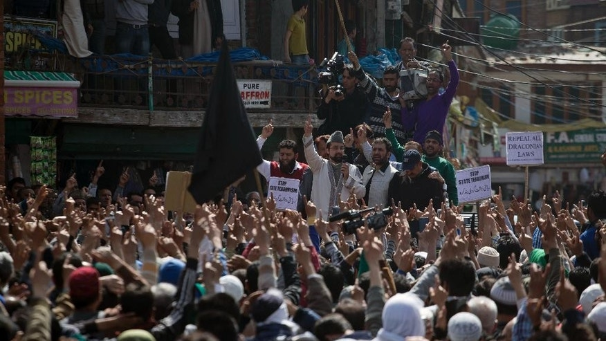 Chairman of All Parties Hurriyat Conference (APHC) Mirwaiz Umar Farooq, center, shouts freedom slogans during a protest in Srinagar, Indian controlled Kashmir, Friday, April 17, 2015. Police fired tear gas and rubber bullets Friday to disperse hundreds of demonstrators in Indian-controlled Kashmir who hurled rocks and chanted anti-Indian and pro-Pakistan slogans to protest the killing of a militant commander's brother. The Indian army said the man was killed in a gunbattle along with a militant on Monday, while his relatives and local residents said he was tortured to death. (AP Photo/Dar Yasin)