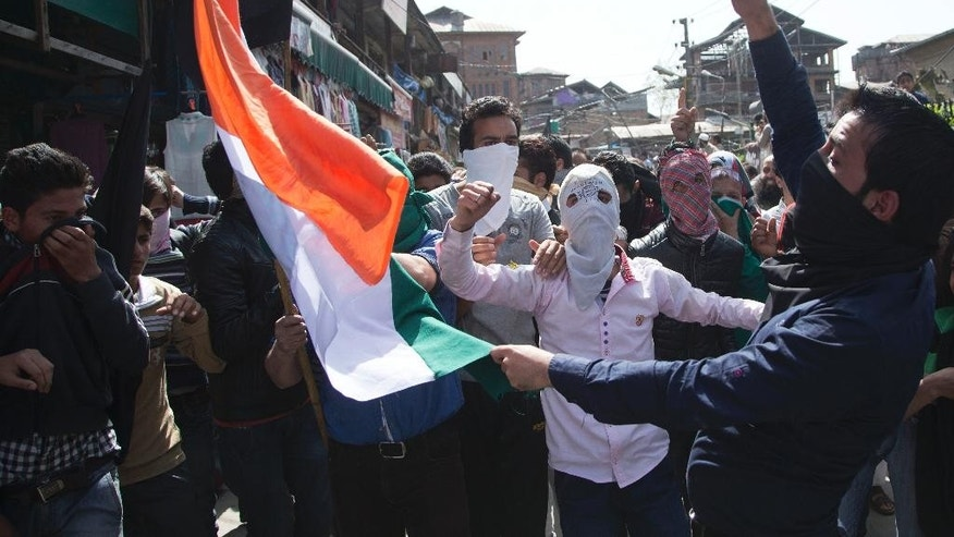 Kashmiri protesters shout slogans as they prepare to burn an Indian flag during a protest in Srinagar, Indian controlled Kashmir, Friday, April 17, 2015. Police fired tear gas and rubber bullets Friday to disperse hundreds of demonstrators in Indian-controlled Kashmir who hurled rocks and chanted anti-Indian and pro-Pakistan slogans to protest the killing of a militant commander's brother. The Indian army said the man was killed in a gunbattle along with a militant on Monday, while his relatives and local residents said he was tortured to death. (AP Photo/Dar Yasin)