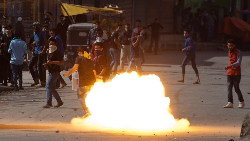 A tear gas shell fired by Indian policemen explodes near Kashmiri protestors in Srinagar, Indian controlled Kashmir, Friday, April 17, 2015. Police fired tear gas and rubber bullets Friday to disperse hundreds of demonstrators in Indian-controlled Kashmir who hurled rocks and chanted anti-Indian and pro-Pakistan slogans to protest the killing of a militant commander's brother. The Indian army said the man was killed in a gunbattle along with a militant on Monday, while his relatives and local residents said he was tortured to death. (AP Photo/Dar Yasin)